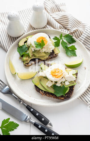 Wholegrain toast with avocado, egg and soft cheese on white plate, healthy breakfast healthy eating concept - Stock Photo
