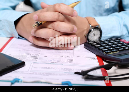 Picture of hand on the form with holding pen. Portrait of clipboard, form, pen, glasses, calculator and phone. - Stock Photo