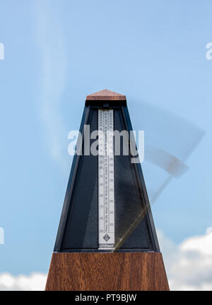 Portrait close up of musical timekeeping metronome in motion against blue sky background. Concept: time movement, time moving fast, time flies - Stock Photo