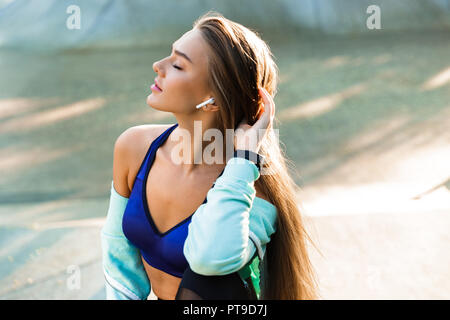 Photo of beautiful young sports lady in park outdoors listening music with earphones. - Stock Photo