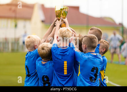 Young Soccer Players Holding Trophy. Boys Celebrating Soccer Football Championship. Winning team of sport tournament for kids children teams. - Stock Photo