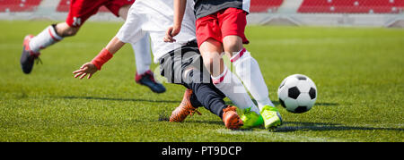Football players in action kicking ball on stadium. Soccer players kicking ball on the green field. Young football players on the football match. Spor - Stock Photo