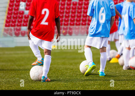 Boys soccer team training. Soccer football players training. Kids playing soccer on a stadium field. A multi-ethnic group of elementary age children p - Stock Photo