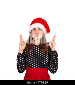 confused woman with raising hands with crossed fingers, making wish to win. emotional girl in santa claus christmas hat isolated on white background.  - Stock Photo