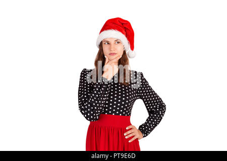 Dreamy attractive, thinking and confident young woman in dress, holding palm on cheek and gazing at upper left corner. emotional girl in santa claus c - Stock Photo
