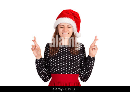 woman in dress smiling broadly, closing eyes and raising crossed fingers while praying and hoping. emotional girl in santa claus christmas hat isolate - Stock Photo