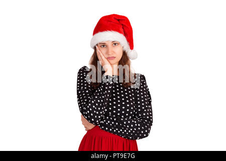 gloomy anxious good-looking woman in dress, frowning and being sad, having troubled. emotional girl in santa claus christmas hat isolated on white bac - Stock Photo