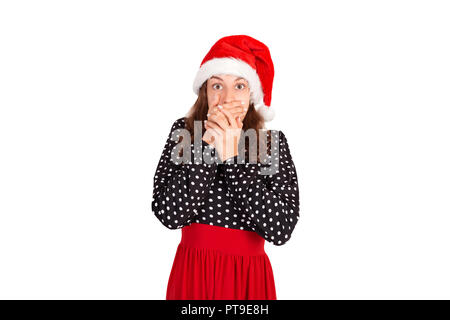 Pretty girl covering her mouth. emotional girl in santa claus christmas hat isolated on white background. holiday concept. - Stock Photo