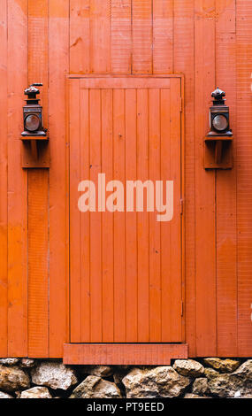 Old orange and red Western door between two old lanterns - Stock Photo