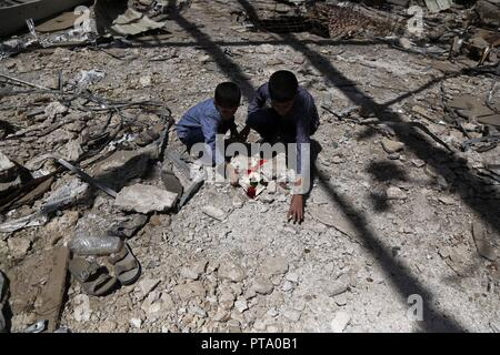 Sanaa, Yemen. 8th Oct, 2018. A victim's children place flowers at the place where their father was killed on the second anniversary of a 2016 funeral hall airstrike in Sanaa, Yemen, on Oct. 8, 2018. Credit: Mohammed Mohammed/Xinhua/Alamy Live News - Stock Photo