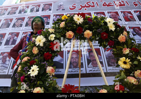 Sanaa, Yemen. 8th Oct, 2018. A man stands by a wreath in front of pictures of victims on the second anniversary of a 2016 funeral hall airstrike in Sanaa, Yemen, on Oct. 8, 2018. Credit: Mohammed Mohammed/Xinhua/Alamy Live News - Stock Photo
