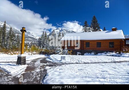 Wooden Log Cabin and Snowy Walking Paths in Spring Creek Mountain Alpine Village Canmore Alberta Canada - Stock Photo