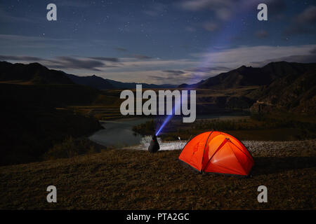 A tourist watches the starry sky near the tent on the background of a beautiful and winding river. - Stock Photo