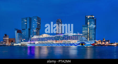 AIDA Perla cruiseship moored at twilight in Rotterdam. It is 300m, has 1643 cabins and 16 passenger decks. - Stock Photo