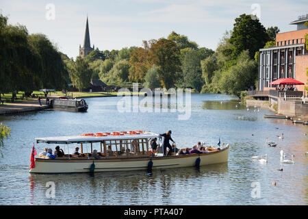 A river cruise ship taking tourists and visitors along the River Avon in Stratford upon Avon on a bright Autumnal day. - Stock Photo