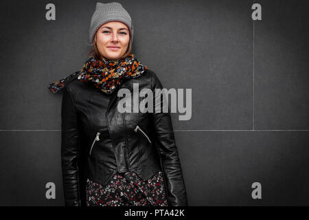 Beautiful modern urban young woman wearing pink knitting hat, black coat and dress. Trendy teenage girl in autumn outdoors. - Stock Photo