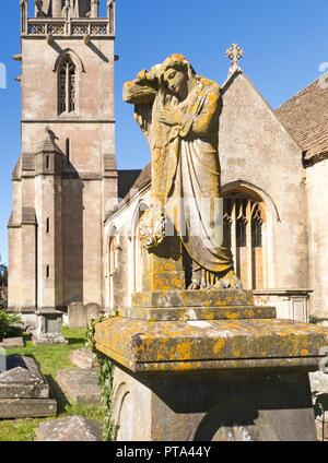 Statue on grave in graveyard of Church of Saint Bartholomew, Corsham, Wiltshire, England, UK - Stock Photo