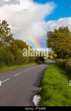 A rainbow over the B4368 Craven Arms to Clun road, reflects the colours in the landscape as autumn colours begin as the trees turn, Shropshire, UK - Stock Photo