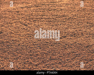 Footprints and service marks on tennis court details. Dry light red crushed bricks surface on outdoor tennis ground. Rough texture against sun - Stock Photo