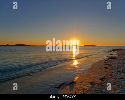 On a beach the setting sun reflects of the waters of the English Channel at Landeda, Brittany. - Stock Photo