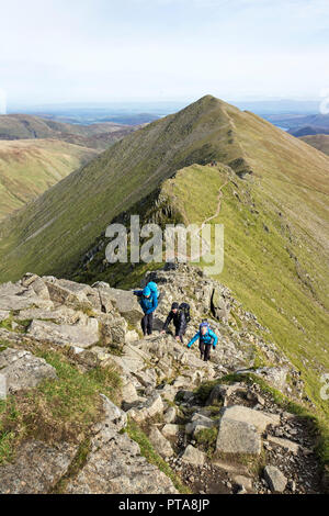 Walkers Scrambling on Swirral Edge with Catstye Cam Behind, Lake District, Cumbria, UK - Stock Photo