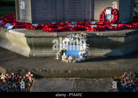 Remembrance Day red poppy wreaths and a white poppy wreath at a war memorial in Chichester, West Sussex, UK. - Stock Photo