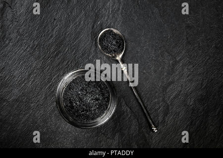 An overhead photo of black caviar in a jar and in a spoon, shot from above on a black background with a place for text - Stock Photo