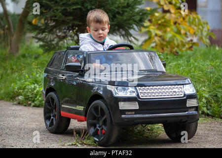 Cute boy in riding a black electric car in the park. Funny boy rides on a toy electric car - Stock Photo