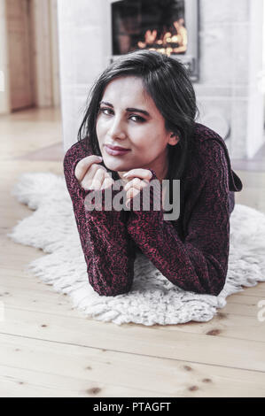 Young, beautiful woman heating in living room (model-released) - Stock Photo