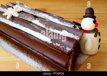Buche de Noel or Chocolate Yule Log Cake for Christmas Celebration with a Cute Snowman Marzipan on a Wooden Table - Stock Photo