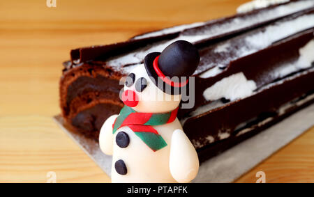 Close-up of a Cute Snowman Marzipan with Blurred Chocolate Yule Log Cake in Background Isolated on Wooden Table - Stock Photo