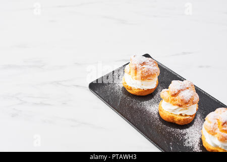 Top view of delicious cream puff cakes with cream and powdered sugar on a black plate on white marble table. Selective focus, copy space. - Stock Photo
