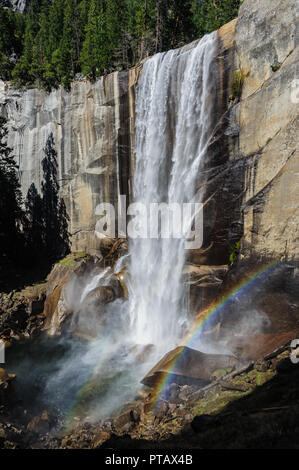 A rainbow showing up in Front Of Vernall Fall, along the Mist Trail, in Yosemite National Park - Stock Photo