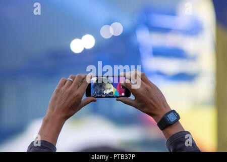 A fan in the crowd videoing EDM duo, Orbital, performing at George Square, Glasgow, Scotland, on 10th August, 2018, during Festival 2018 - Stock Photo