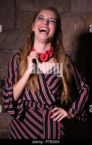 Young woman (laughing) with blonde hair, wearing a striped dress, large necklace and earrings, photographed in a studio with creative lighting - Stock Photo