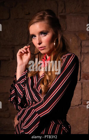 Young woman with blonde hair, wearing a striped dress, large necklace and earrings, photographed in a studio with creative lighting - Stock Photo