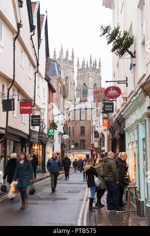 York, UK – 12 Dec 2016: A Christmas shoppers throng the busy pedestrian lanes of York's historic old town on 12 Dec at Low Petergate, York - Stock Photo