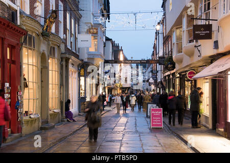 York, UK – 12 Dec 2016: A homeless man sits ignored ina doorway as Christmas shoppers throng the busy pedestrian lanes of York's historic old town on  - Stock Photo