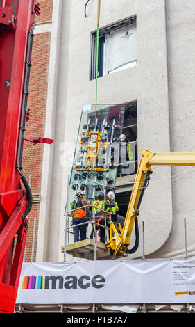 Building contractor Mace workers on a cherry picker hoist carefully fitting a large new glass window pane into a building in Mayfair, London, UK - Stock Photo