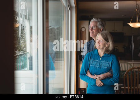 Senior couple embracing each other at home - Stock Photo