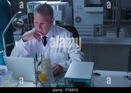 Male scientist using laptop in laboratory - Stock Photo