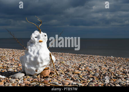 A snowman on the beach at Budleigh Salterton in Devon, England. 20 March 2018 - Stock Photo