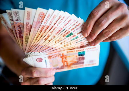 Russian rubles in the hand of a fan.male hand holding many of the Russian banknotes.The transfer of money.The isolated five-thousandth of Russian rubles denominations in a hand - Stock Photo