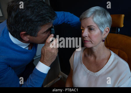 Optometrist examining patient eyes with ophthalmoscope - Stock Photo