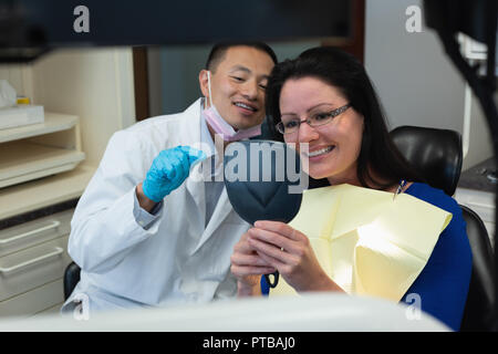 Male dentist interacting with patient - Stock Photo