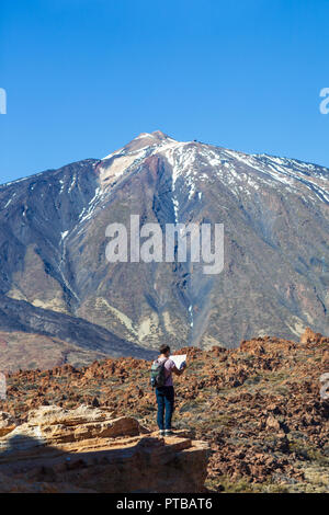 Lost hiker checks map to find directions standing on the edge of rock with volcano El Teide on background. National park of Tenerife, Canary Islands,  - Stock Photo