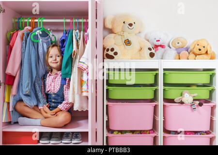 A little child girl is sitting in a wardrobe in a children's room. Saving and storage system for children's things and toys concept. - Stock Photo