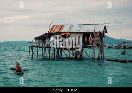 stilt houses in a bajau sea gypsy village next to a small island rock outcrop - Stock Photo