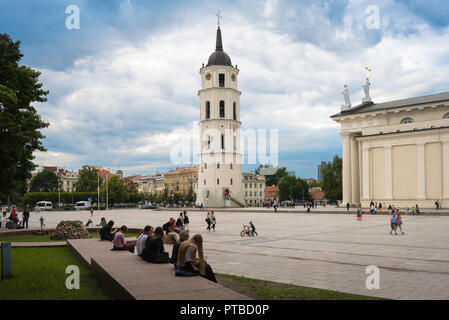 Vilnius Cathedral Square, view of people sitting in Cathedral Square with the Belfry tower and west end of the cathedral in the distance, Lithuania. - Stock Photo