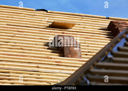 A number of roofing tiles stacked against tile batten on a roof waiting to be laid on an a new extension of a building - Stock Photo